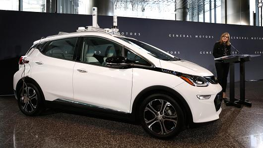Mary Barra, chief executive officer of General Motors Co. (GM), stands next to a Chevrolet Bolt EV self-driving test car while speaking during a news conference at GM's headquarters in the Renaissance Center in Detroit, Michigan, U.S., on Thursday, Dec. 15, 2016.