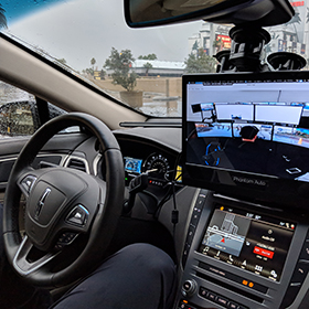 The view inside a Phantom car shows a hands free passenger in the driver's seat, as well as a special display showing the remote driver of the car.