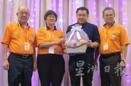 甲日间师训同学会主席周凤兰(左二)赠送水果礼篮予晚宴开幕人颜天禄(右二)。(马来西亚《星洲日报》)