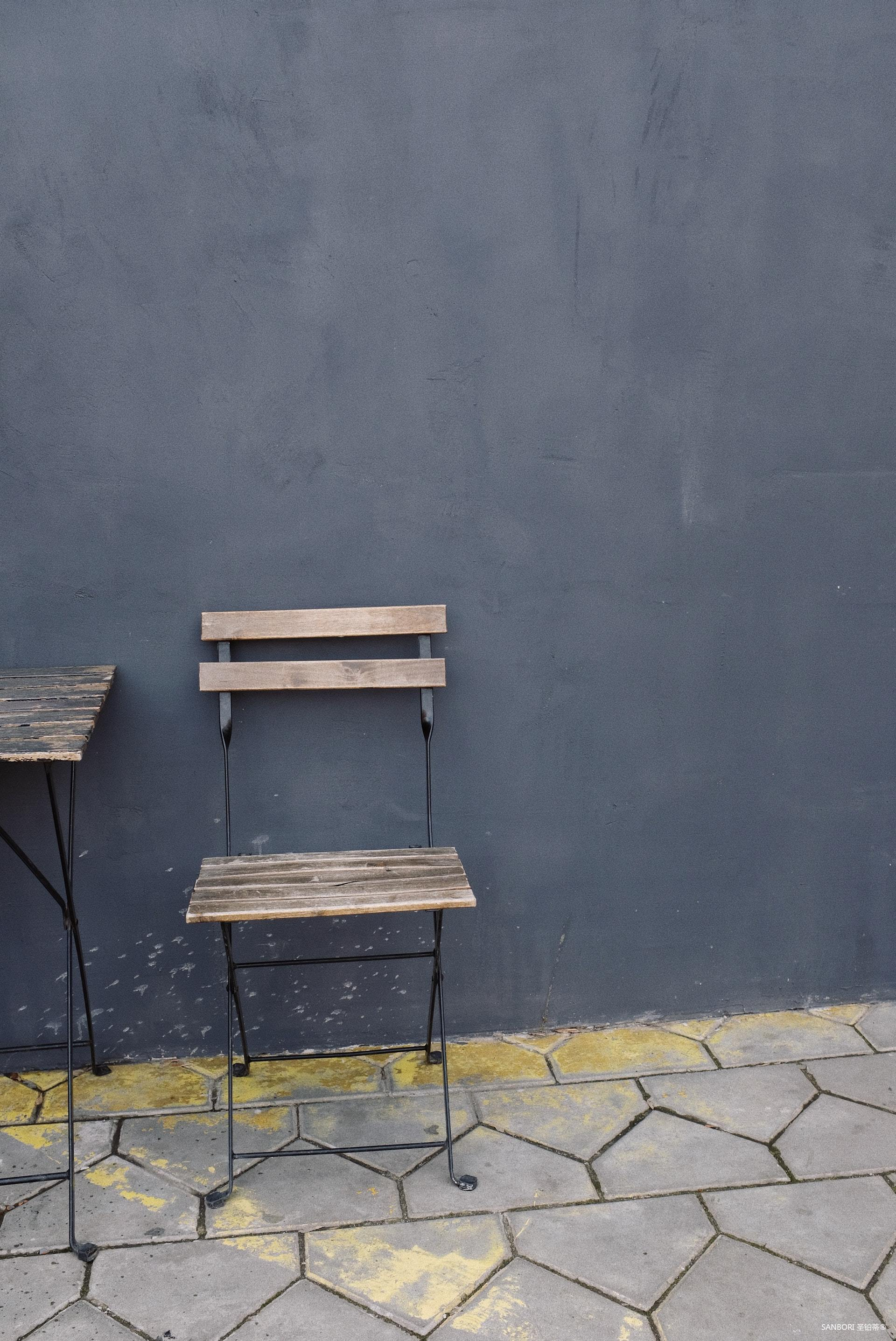 wooden-chair-and-table-placed-near-gray-wall-on-street-3964344.jpg