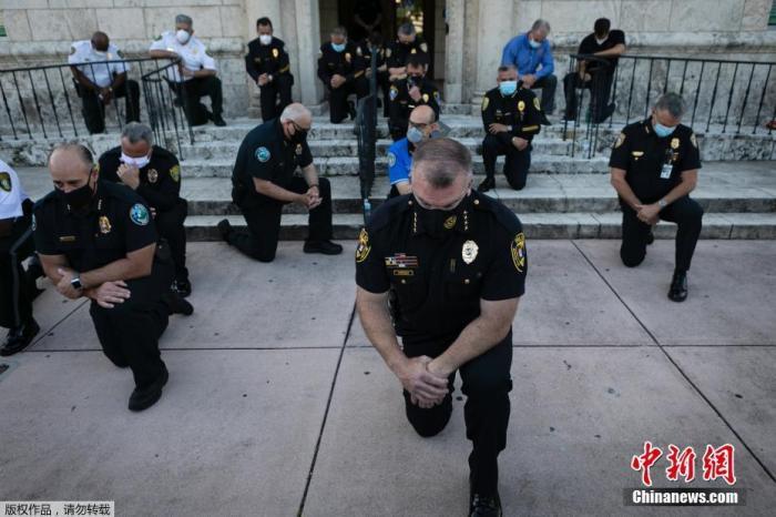 """5月30日,美国佛罗里达州,警察们单膝下跪声援""""黑人的命也是命""""运动。美国黑人乔治·弗洛伊德在手无寸铁的情况下被明尼阿波利斯警察逮捕并压在地上直至其死亡。Eva Marie UZCATEGUI 摄"""